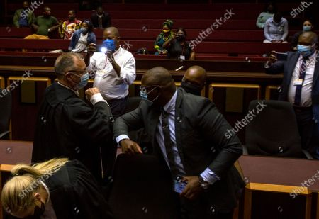 State prosecutor Advocate Billy Downer, left, greets members of the legal team representing former President Jacob Zuma, inside the High Court in Pietermaritzburg, South Africa, . A South African judge said he will file a criminal complaint against former South African president Jacob Zuma after he staged a dramatic walkout while attending a commission of inquiry looking into corruption during his tenure from 2009 to 2018
