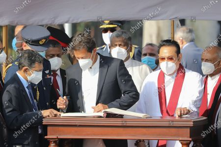 Pakistan's Prime Minister Imran Khan (4-L) signs the special visitors' book while Sri Lankan Prime Minister Mahinda Rajapaksa (2-R) looks on at the Bandaranaike International Airport in Colombo, Sri Lanka, 23 February 2021. Khan is on a two-day official visit to Sri Lanka.