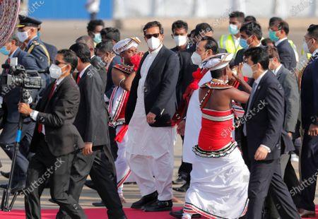 Pakistan's Prime Minister Imran Khan, center, walks with Sri Lankan Prime Minister Mahinda Rajapaksa upon his arrival in Colombo, Sri Lanka, . Khan is in Sri Lanka for a two day official visit