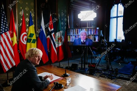 British Prime Minister Boris Johnson, listens to a video link from David Attenborough, broadcaster and natural historian, during UN Security Council's virtual meeting on climate change risks in London, Britain, 23 February 2021 Wealthy nations will come under pressure to boost funding to tackle climate change during the United Nations discussion that will warn how unchecked rising temperatures could lead to wars and mass migration. Photographer: Hollie Adams/Bloomberg
