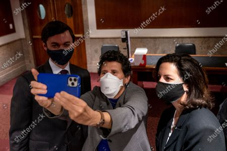 Stock Photo of Sen. Jon Ossoff, D-Ga., left, takes a selfie with attorneys representing former U.S. Capitol Police Chief Steven Sund, Debra Katz, center, and Lisa Banks, right, following a Senate Homeland Security and Governmental Affairs & Senate Rules and Administration joint hearing on Capitol Hill, Washington, to examine the January 6th attack on the Capitol