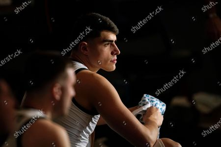 Iowa center Luka Garza sits on the bench during player introductions before an NCAA college basketball game against Penn State, in Iowa City, Iowa