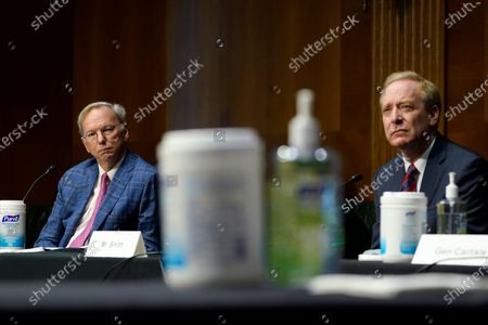 Dr. Eric E. Schmidt, co-founder of Schmidt Futures, left, and Brad Smith, president of Microsoft Corporation, right, listens on Capitol Hill in Washington, during a hearing on emerging technologies and their impact on national security