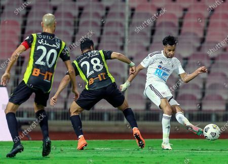 Al-Ittihad's players Hamed Al-Mansour (C) and Karim El Ahmadi (L) in action against Al-Faisaly's Ahmed Ashraf (R) during the Saudi Professional League soccer match between Al-Ittihad and Al-Faisaly at King Abdulaziz Stadium, in Mecca, Saudi Arabia, 23 February 2021.