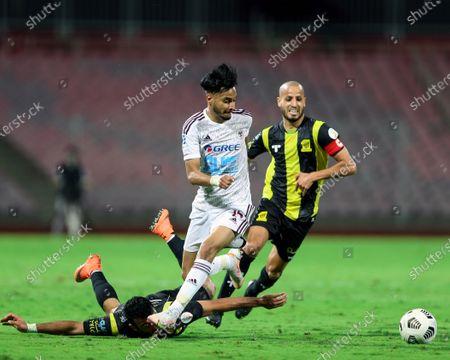 Al-Ittihad's players Hamed Al-Mansour (down) and Karim El Ahmadi (R) in action against Al-Faisaly's Ahmed Ashraf (front) during the Saudi Professional League soccer match between Al-Ittihad and Al-Faisaly at King Abdulaziz Stadium, in Mecca, Saudi Arabia, 23 February 2021.