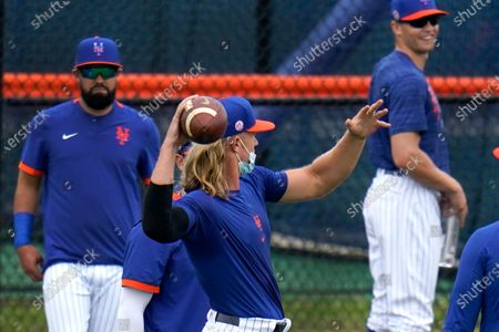 New York Mets pitcher Noah Syndergaard, center, tosses a football as teammates Luis Guillorme, left, and Brandon Nimmo, right, watch during spring training baseball practice, in Port St. Lucie, Fla