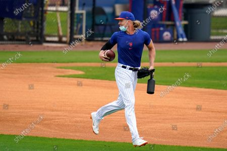New York Mets pitcher Noah Syndergaard runs with a football during spring training baseball practice, in Port St. Lucie, Fla