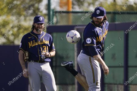 Milwaukee Brewers pitcher Ray Black, right, plays with a soccer ball as teammate Bobby Wahl watches during the team's spring training baseball workout in Phoenix