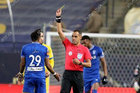 Uruguayan referee Esteban Ostojich (2-R) issues a yellow card for Al-Hilal's Salem Al-Dawsari (L) during the Saudi Professional League soccer match between Al-Nassr and Al-Hilal at King Saud University Stadium, in Riyadh, Saudi Arabia, 23 February 2021.