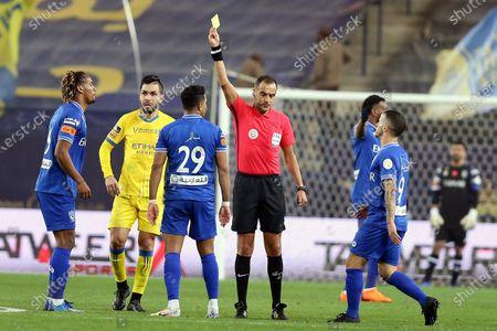 Uruguayan referee Esteban Ostojich (C) issues a yellow card for Al-Hilal's Salem Al-Dawsari (3-L) during the Saudi Professional League soccer match between Al-Nassr and Al-Hilal at King Saud University Stadium, in Riyadh, Saudi Arabia, 23 February 2021.