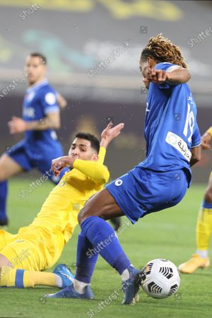 Stock Photo of Al-Nassr's player Sultan Al-Ghannam (L) in action against Al-Hilal's Andre Carrillo (R) during the Saudi Professional League soccer match between Al-Nassr and Al-Hilal at King Saud University Stadium, in Riyadh, Saudi Arabia, 23 February 2021.