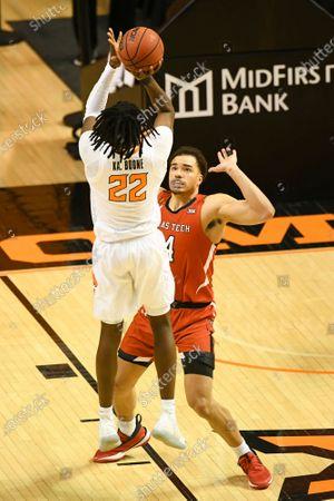 Oklahoma State forward Kalib Boone (22) takes a shot at the basket over the Texas Tech forward Marcus Santos-Silva (14) during an NCAA college basketball game, in Stillwater, Okla