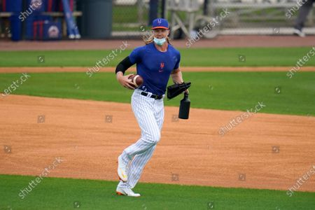 Stock Image of New York Mets pitcher Noah Syndergaard runs with a football during spring training baseball practice, in Port St. Lucie, Fla