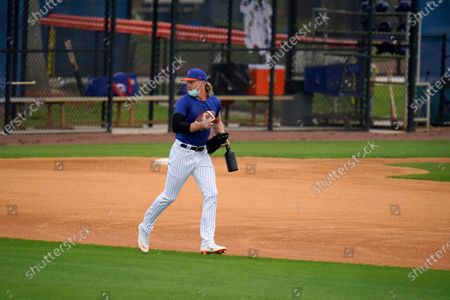 Stock Picture of New York Mets pitcher Noah Syndergaard runs with a football during spring training baseball practice, in Port St. Lucie, Fla