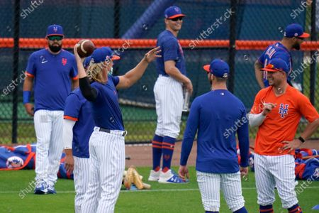 New York Mets pitcher Noah Syndergaard tosses a football as teammates watch during spring training baseball practice, in Port St. Lucie, Fla