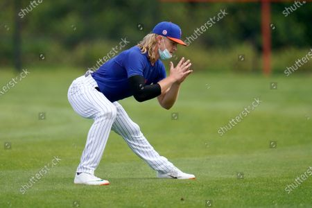 New York Mets pitcher Noah Syndergaard stretches during spring training baseball practice, in Port St. Lucie, Fla