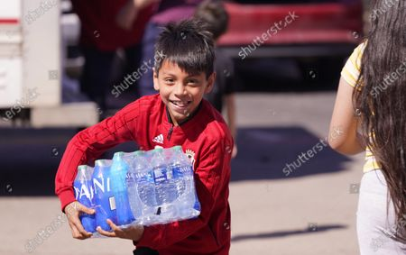 Stock Photo of Diego Garcia, 9, carries driking water he was given by volunteers at an apartment complex without water, in Dallas. Two local bartenders took it upon themselves to bring a truck of drinking water to distribute to residents that have not had running water for over a week