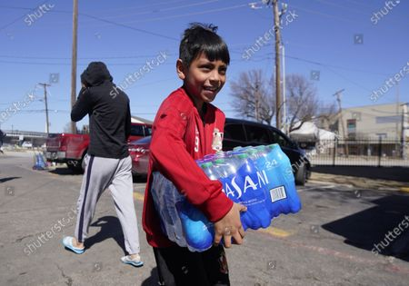 Stock Picture of Diego Garcia, 9, carries drinking water he was given by volunteers at an apartment complex without water, in Dallas. Two local bartenders took it upon themselves to bring a truck of drinking water to distribute to residents that have not had running water for over a week