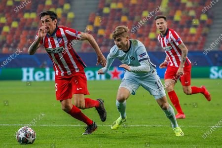 Chelsea's Timo Werner, center, runs for the ball next to Atletico Madrid's Lucas Torreira during the Champions League, round of 16, first leg soccer match between Atletico Madrid and Chelsea at the National Arena stadium in Bucharest, Romania