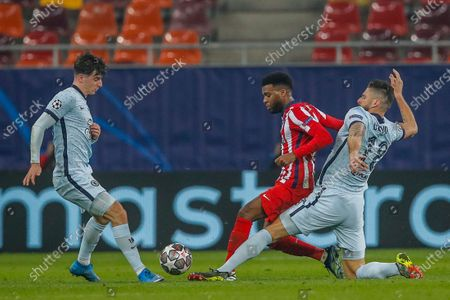 Atletico Madrid's Thomas Lemar, center, vies for the ball with Chelsea's Olivier Giroud, right, during the Champions League, round of 16, first leg soccer match between Atletico Madrid and Chelsea at the National Arena stadium in Bucharest, Romania