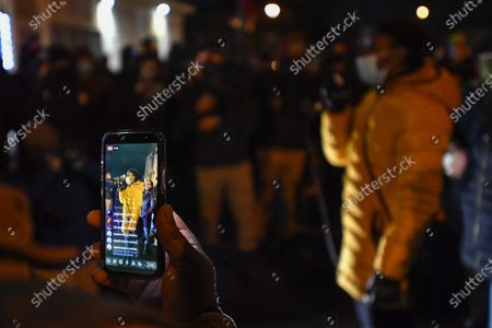 Cell phone live streams as Stanley Martin, right, addresses the crowd gathered at the site of Daniel Prude's encounter with police officers a year ago in Rochester, N.Y., . A grand jury voted not to charge officers shown on body camera video holding Daniel Prude down naked and handcuffed on a city street last winter until he stopped breathing. New York Attorney General Letitia James announced the decision Tuesday. The 41-year-old Black man's death last March sparked nightly protests in Rochester, New York, after the video was released nearly six months later