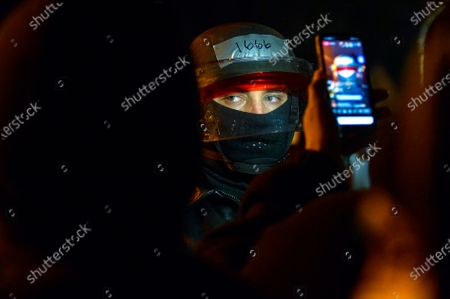 Police officer's face is illuminated by a protester's cellphone as a crowd surrounds a police substation in Rochester, N.Y., late . A grand jury voted not to charge officers shown on body camera video holding Daniel Prude down naked and handcuffed on a city street last winter until he stopped breathing. New York Attorney General Letitia James announced the decision Tuesday. The 41-year-old Black man's death last March sparked nightly protests in Rochester after the video was released nearly six months later