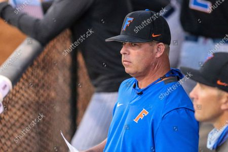 Florida coach Kevin O'Sullivan stands in the dugout during the team's NCAA college baseball game against North Florida, in Jacksonville, Fla