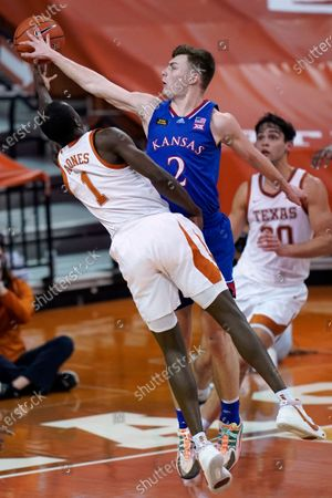 Kansas guard Christian Braun (2) blocks a shot by Texas guard Andrew Jones (1) during overtime in an NCAA college basketball game, in Austin, Texas