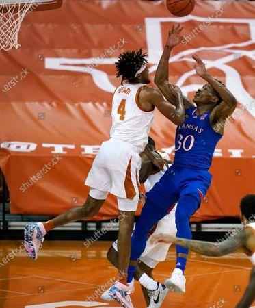 Kansas guard Ochai Agbaji (30) shoots over Texas forward Greg Brown (4) during the first half of an NCAA college basketball game, in Austin, Texas