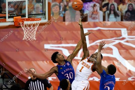 Texas guard Andrew Jones (1) drives to the basket between Kansas guard Ochai Agbaji (30) and guard Bryce Thompson, right, during the second half of an NCAA college basketball game, in Austin, Texas