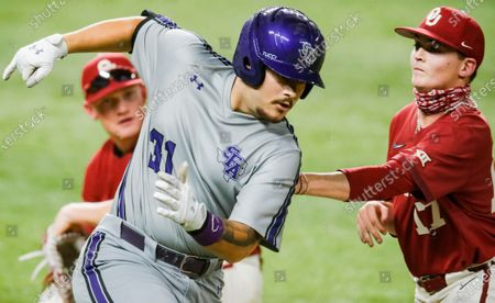 Oklahoma pitcher Aaron Brooks (17) attempts to tag out Stephen F. Austin's Jake Zarrello (31) in the sixth inning during an NCAA baseball game, in Arlington, Texas. The home plate umpire ruled that Zarrello was impeded while running to first on the play