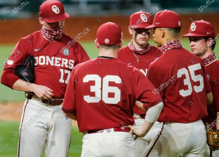 Oklahoma pitcher Aaron Brooks (17) is relieved by pitcher Javier Ramos (35) after giving up three runs in the sixth inning during an NCAA baseball game against Stephen F. Austin, in Arlington, Texas