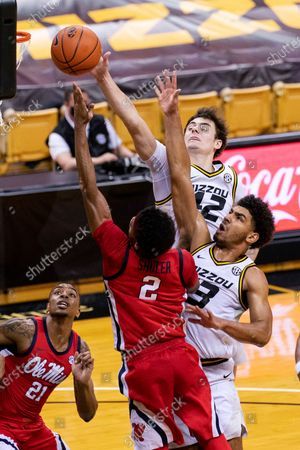 Mississippi's Devontae Shuler (2) and Missouri's Mark Smith, right, and Parker Braun, top, reach for a rebound during the first half of an NCAA college basketball game, in Columbia, Mo