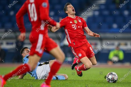 Robert Lewandowski of Bayern München is tackled by Gonzalo Escalante of SS Lazio during the UEFA Champions League Round of 16 match between Lazio Roma and Bayern München at Olimpico Stadium on February 23, 2021 in Rome, Italy. Bayern München won the match 4-1.