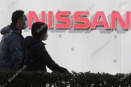 "People walk past the corporate logo at Nissan Motor Co.'s global headquarters in Yokohama, near Tokyo. Former Nissan Chief Executive Hiroto Saikawa told a Japanese court, he believed the compensation for his predecessor Carlos Ghosn was too low ""by international standards,"" and so he supported Ghosn's retirement packages to prevent him from leaving"