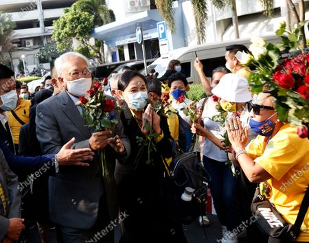 Thai former anti-government protest leader Suthep Thaugsuban (L) receives flowers from supporters as he arrives for a hearing at the Criminal Court, in Bangkok, Thailand, 24 February 2021. A Thai court will rule on 24 February in the trial of former anti-government protesters from the People's Democratic Reform Committee, including former MP Suthep Thaugsuban, Education Minister Nataphol Teepsuwan, and the Digital Economy and Society Minister Buddhipongse Punnakanta, in connection to street demonstrations against the government of former Prime Minister Yingluck Shinawatra in 2013-14. The charges include insurrection, illegal assembly and obstructing elections.