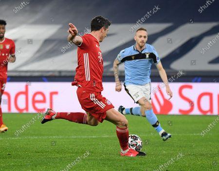 Bayern Munich's Robert Lewandowski (L) scores during a UEFA Champions League round of 16 first leg football match between Lazio and Bayern Munich in Rome, Italy, Feb. 23, 2021.