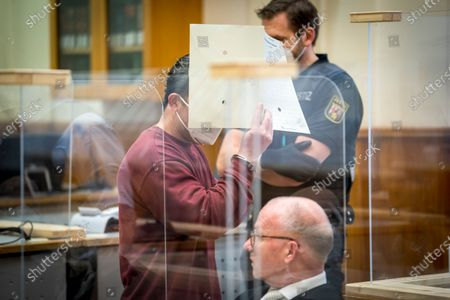 Syrian defendant Eyad Al-Gharib hides his face as he arrives to his hear his verdict in a court room in Koblenz, Germany, . A German court has convicted the former member of Syrian President Bashar Assad's secret police of facilitating the torture of prisoners in a landmark ruling that human rights campaigners hope will set a precedent for other cases