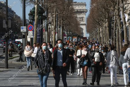 People wearing face masks to prevent the spread of coronavirus make their way along the Champs-Elysees avenue in Paris, . France may need to impose new local restrictions to deal with a worsening Covid-19 situation as it scrambles to avoid a new national lockdown, the government spokesman Gabriel Attal told reporters Wednesday