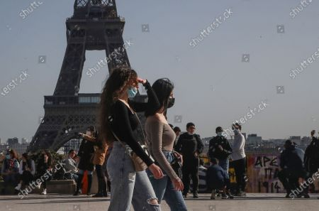 People wearing face masks to prevent the spread of coronavirus walks at Trocadero plaza near Eiffel Tower in Paris, . France may need to impose new local restrictions to deal with a worsening Covid-19 situation as it scrambles to avoid a new national lockdown, the government spokesman Gabriel Attal told reporters Wednesday