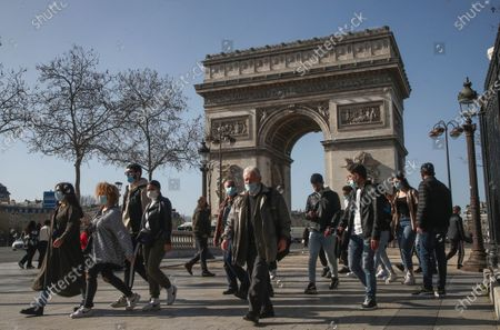 People wearing wearing face masks to prevent the spread of coronavirus make their way at the Champs-Elysees avenue in Paris, . France may need to impose new local restrictions to deal with a worsening Covid-19 situation as it scrambles to avoid a new national lockdown, the government spokesman Gabriel Attal told reporters Wednesday