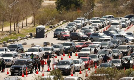 Staff appears to push a vehicle that may have run out of gas while waiting in line as Los Angeles resumes COVID-19 vaccinations Tuesday at the Hansen Dam vaccination site including several other large-scale sites in L.A. that were forced to close late last week when shipments containing at least 63,000 does of COVID-19 vaccines were held up due to a winter storm battering much of the country. COVID-19 vaccinations resume with priority to those who lost appointments. With 92,000 does of the Moderna vaccine arriving in L.A. the city resumed vaccinations. Hansen Dam on Tuesday, Feb. 23, 2021 in Los Angeles, CA. (Al Seib / Los Angeles Times).