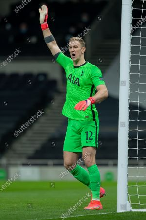 Goalkeeper Joe Hart of Tottenham Hotspur holds his arm up and shouts instructions to his defence