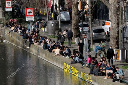 People sunbathe along the Canal Saint Martin in Paris, as temperatures hit 19 degrees Celsius (62 Fahrenheit) . France may need to impose new local restrictions to deal with a worsening Covid-19 situation as it scrambles to avoid a new national lockdown, the government spokesman Gabriel Attal told reporters Wednesday