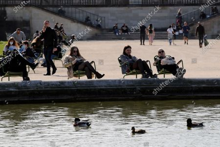 People sunbathe at the Tuileries garden in Paris, as temperatures hit 19 degrees Celsius (62 Fahrenheit) . France may need to impose new local restrictions to deal with a worsening Covid-19 situation as it scrambles to avoid a new national lockdown, the government spokesman Gabriel Attal told reporters Wednesday