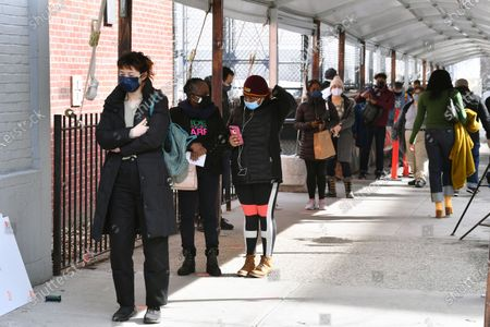 Members of the public are seen queuing outside the Medgar Evers mass vaccination site in Brooklyn.