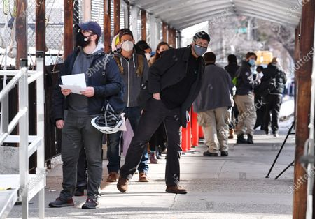 Members of the public are seen queuing outside the Medgar Evers mass vaccination site in Brooklyn