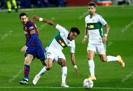 FC Barcelona's striker Lionel Messi (L) vies for the ball with Elche's defender Johan Mojica (C) during the Spanish LaLiga soccer match between FC Barcelona and Elche CF held at Camp Nou stadium, in Barcelona, Spain, 24 February 2021.