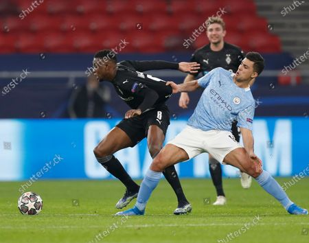 Moenchengladbach's Denis Zakaria, left, is pulled by Manchester City's Rodrigo during the Champions League round of 16 first leg soccer match between Borussia Monchengladbach and Manchester City at the Puskas Arena stadium in Budapest, Hungary