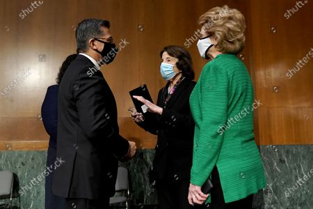 Sens. Dianne Feinstein (D-Calif.) and Debbie Stabenow (D-Mich.) speaks to Xavier Becerra, nominee for Secretary of Health and Human Services, as they arrive for his Senate Finance Committee nomination hearing on Capitol Hill in Washington, DC, USA, 24 February 2021.